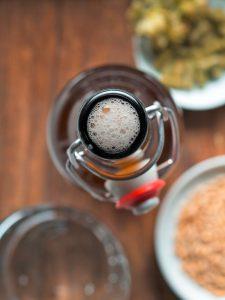 Geöffnete Bier-Bügelverschlussflasche und Bier-Zutaten.
