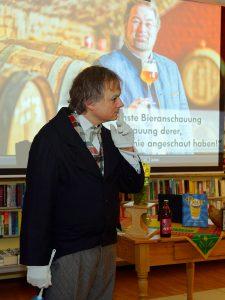Butler Dirk Bayer bittet das Publikum um Ruhe.