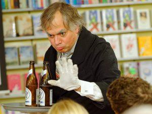 Butler Dirk Bayer bringt eine Maiels Weisse zu den Gästen.