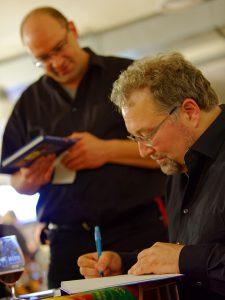 Interessierte Teilnehmer der Bier-Genuss-Lesung holen sich im Anschluss ihre persönliche Widmung von Biersommelier Markus Raupach.