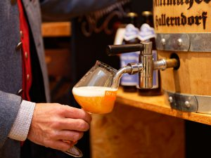 """Das erste Glas des neuen Bamberger Bieres """"Weiße Taube"""" läuft aus dem Fass."""