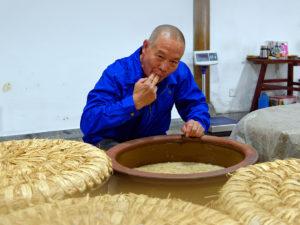 Reisweinmeister Guanxian Wang testet den Stand der Vergärung seines Reisweines